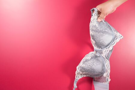 Women holding a bra against pink background. Concept of Breast cancer awareness and international no bra day celebration