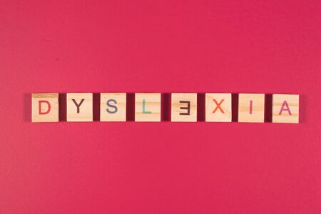 wooden alphabet blocks with DYSLEXIA word on pink background. Concept of Dyslexia awareness and human brain development