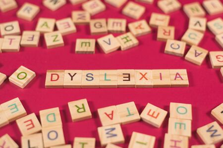 high angle view of a wooden alphabet blocks with DYSLEXIA word in the center on pink background. Concept of Dyslexia awareness and human brain development