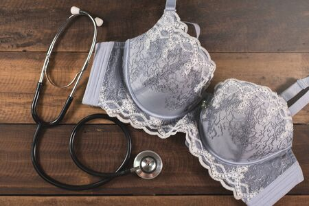 Bra and a Stethoscope on a wooden table. Concept of women health care and breast cancer awareness 免版税图像