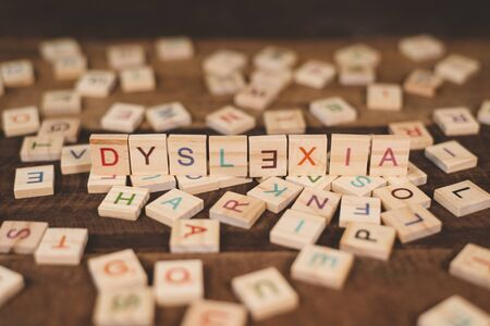 high angle view of a wooden alphabet blocks with DYSLEXIA word in the center on wooden table. Concept of Dyslexia awareness and human brain development 免版税图像