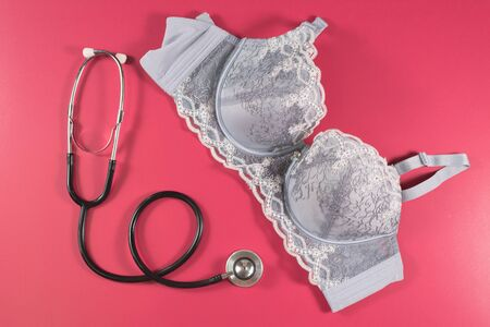 Bra and a Stethoscope on a pink background. Concept of women health care and breast cancer awareness Фото со стока