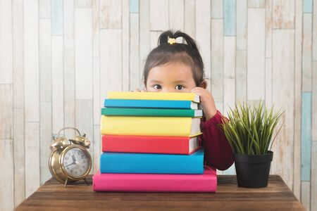 cute little asian girl peeping from behind stack of books. Concept of education, couriousity and child growth development