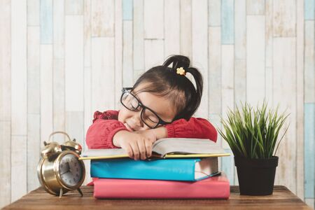 Cute little asian girl fall asleep while studying. Concept of education and tiredness Foto de archivo - 131054299