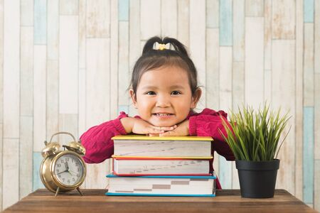 adorable little asian girl smiling while looking at camera with books on table. Concept of education and child growth development