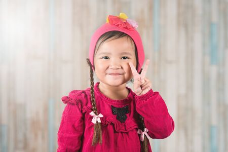 Cute little asian girl showing PEACE hand gesture. Concept of happiness and carefree