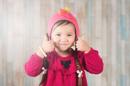 cute little asian girl wearing casual clothing gesturing two thumbs up. Concept of Happiness and satisfaction Фото со стока