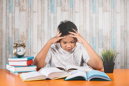 Stressed college student learning hard with books in exams preparation feeling overwhelmed, depressed and exhausted while holding his head because of headache. Concept of education, strees, depression and health care Фото со стока - 131274944
