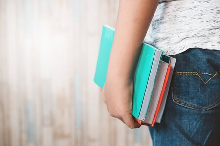 tight shot of teenage midsection holding a colorful books. concept of education, student and lifestyle