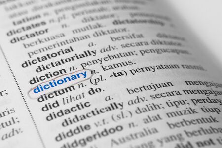 close up of a marked or highlited DICTIONARY word in english to malay dictionary. translator and language concept. Black and white monochrome image with selective colour and soft focus