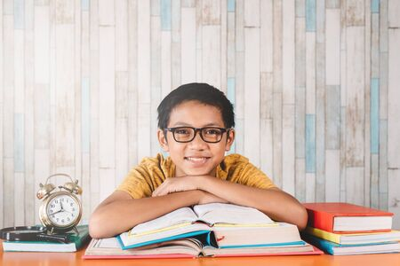 young attractive asian male student smiling while looking at camera sitting against table with books. Concept of education, happy student and expression