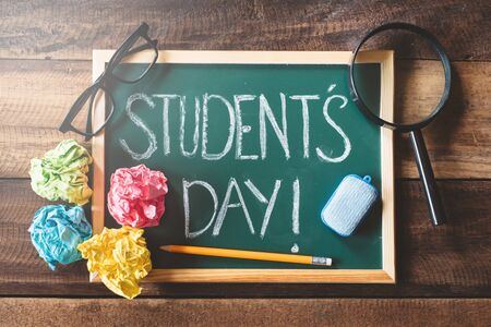 green chalkboard with handwritten STUDENT'S DAY word on wooden table. concept of student day celebration