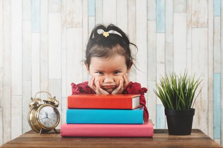 little asian girl with moody face sitting against table with books. Concept of education, laziness, child growth and mood