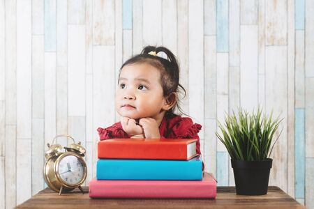 Cute little asian girl gazing and looking at empty space against books on table. Concept of education, future and daydreaming