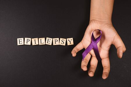 Purple ribbon on cramps hand and EPILEPSY word against black background. Concept of epilepsy awareness 免版税图像