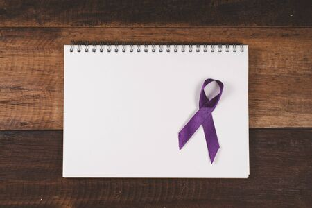 Purple ribbon on a blank notebook for copy space. Concept of epilepsy and alzheimer awareness 免版税图像
