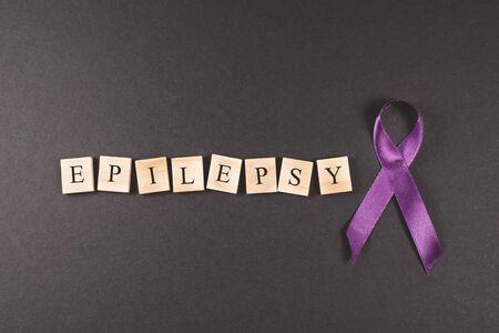 Purple ribbon and EPILEPSY word on black background. Concept of epilepsy awareness