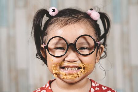 cute little girl with mouth smeared with peanut butter. Concept of penut butter lover