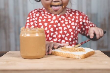 little asian girl spreading  a peanut butter on a white bread. Concept of peanut butter lover Фото со стока