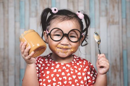 little asian girl holding and enjoying peanut butter in jar and a spoon, Concept of peanut butter lover