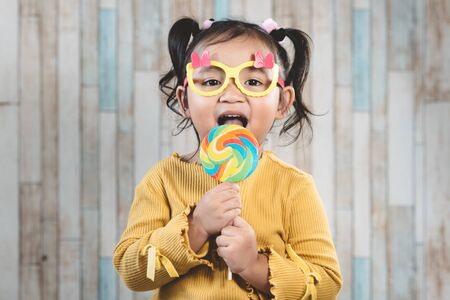 Cute little asian girl holding and eating a colorful lollipop. concept of oral care and candy day