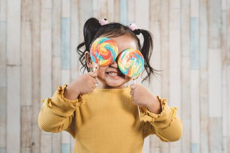 Cute little asian girl holding and eating a colorful lollipop. concept of oral care and candy day Foto de archivo - 132395683