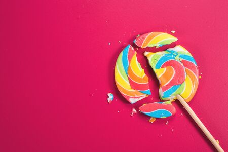 Swirl round broken lollipop on pink background. concept of unhealthy food,sweets and candy day