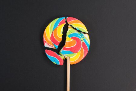 Swirl round broken lollipop on black background. concept of unhealthy food,sweets and candy day Foto de archivo - 132468159