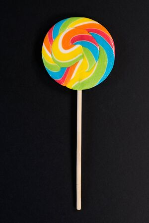 Swirl round lollipop on black background. concept of unhealthy food,sweets and candy day