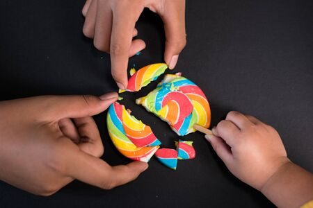Child sharing lollipop on black background, concept of sharing,friendship,togetherness and teamwork