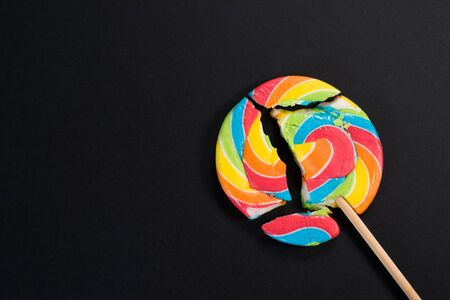 Swirl round broken lollipop on black background. concept of unhealthy food,sweets and candy day