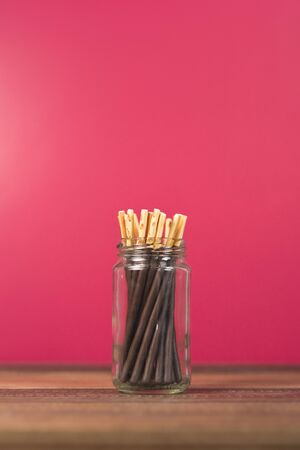pocky chocolate dipped stick in a mason jar on a wooden table. Concept of sweet food and confectionery