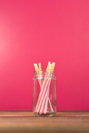 pocky strawberry dipped stick in a mason jar on a wooden table. Concept of sweet food and confectionery Фото со стока