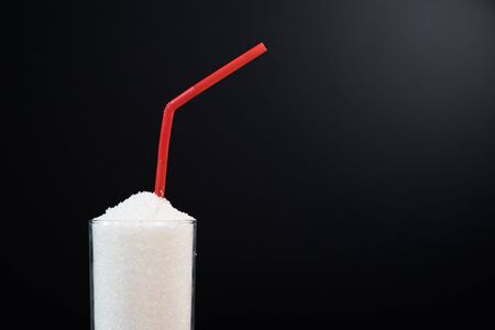 A glass full of white sugar with straw against black background. Concept of unhealthy eating and diabetis 免版税图像