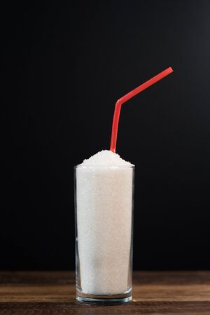 A glass full of white sugar with straw against black background. Concept of unhealthy eating and diabetis. Vertical image