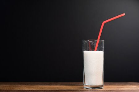 A glass full of white sugar with straw against black background. Concept of unhealthy eating and diabetis 免版税图像 - 134074694