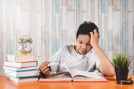 Stressed college student learning hard with books in exams preparation feeling overwhelmed, depressed and exhausted while holding his head because of headache. Concept of education, strees, depression and health care