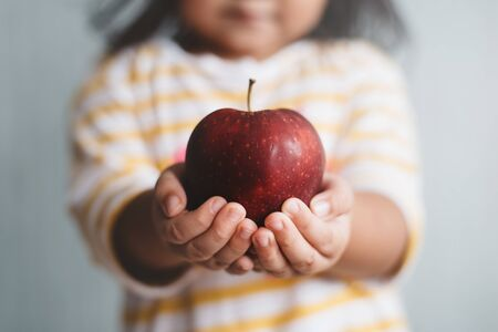 little child holding a red apple in her hand with selective and shallow depth of field blurry image. Concept of Agriculture, healthy eating and symbol of knowledge