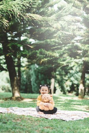 Little asian girl hugging her teddy bear in a park. Concept of happiness and childhood 스톡 콘텐츠