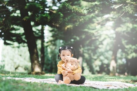 Little asian girl hugging her teddy bear in a park. Concept of happiness and childhood 免版税图像