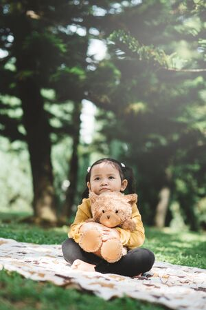 Little asian girl sitting in park while hugging her teddy bear with sad face. Concept of childhood and loneliness