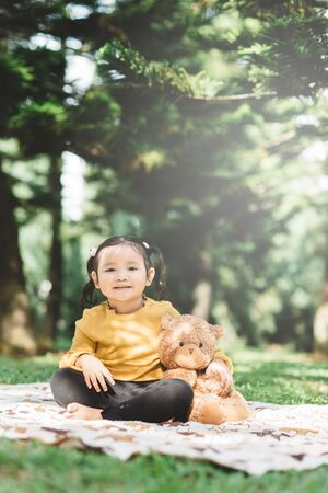 Little asian girl hugging her teddy bear in a park. Concept of happiness and childhood 版權商用圖片