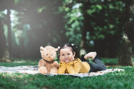 little asian girl lying down beside her teddy bear. Concept of childhood and tenderness 스톡 콘텐츠