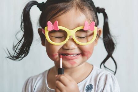 Cute little asian girl playing with toy make up and applying lipstick to her lips. Concept of beauty and childhood 免版税图像 - 139348480