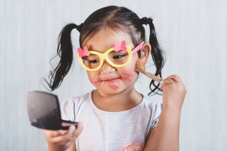 little asian girl playing with makeup blusher brush with dingy face. Concept of beauty and childhood 免版税图像