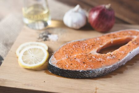 Fresh uncooked salmon on a wooden cutting board. Concept of diet menu and cooking ingredient