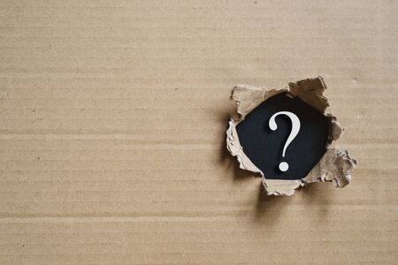 Torned corrugated box revealing question mark. Concept of mystery and uncertainty 스톡 콘텐츠