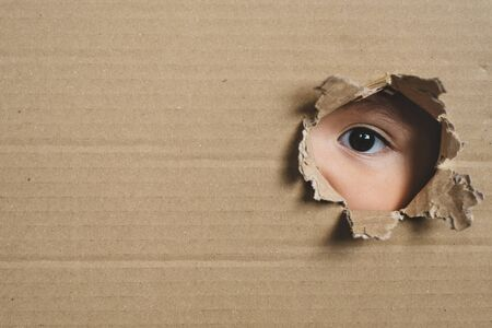 A child eye looking through a hole on a cardboard box. Conept of spy and stalker