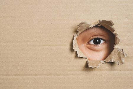 Boy eye peeking through a hole on a cardboard box with shocking gesture. Concept of mystery, secret and stalker