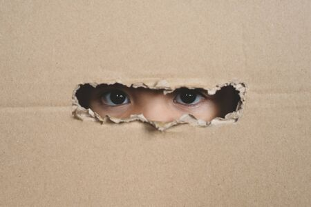 A child eye looking through a hole on a cardboard box. Concept of spy and stalker